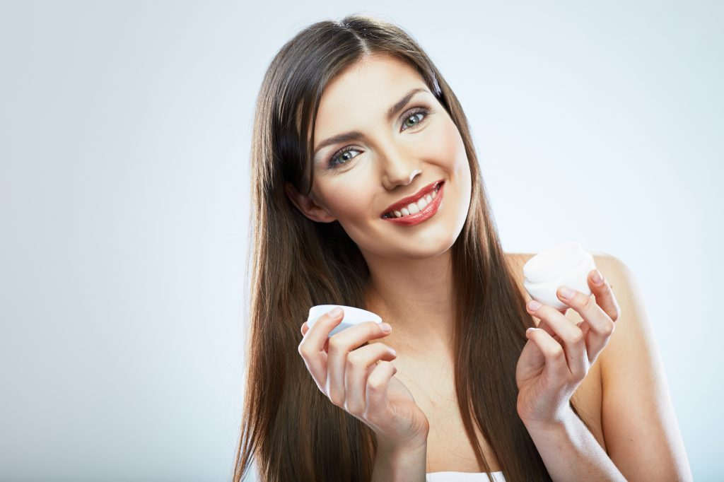 Beauty woman hold face cream. Smiling model with long hair.